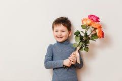 Όμορφο εύθυμο αγόρι με μια ανθοδέσμη των τριαντάφυλλων σε ένα άσπρο υπόβαθρο στοκ φωτογραφίες με δικαίωμα ελεύθερης χρήσης