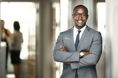 Όμορφο εύθυμο εκτελεστικό επιχειρησιακό άτομο αφροαμερικάνων στο γραφείο χώρου εργασίας στοκ φωτογραφία με δικαίωμα ελεύθερης χρήσης
