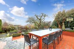 Όμορφο ελατήριο backyad με το επιτραπέζιο σύνολο patio Στοκ Φωτογραφία