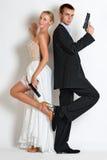 Όμορφο ζεύγος κατασκόπων στο φόρεμα βραδιού με πυροβόλα όπλα Στοκ Φωτογραφίες