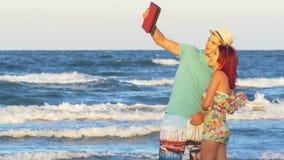 Όμορφο ζεύγος που διατηρεί επαφή με τους φίλους με μια ταμπλέτα στην τηλεοπτική κλήση θαλασσίως απόθεμα βίντεο