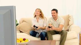 Όμορφο ζεύγος που παίζει ένα τηλεοπτικό παιχνίδι απόθεμα βίντεο