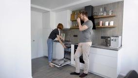 Όμορφο ζεύγος που φορτώνει ένα πλυντήριο πιάτων με βρώμικα πιάτα, φλυτζάνια και επιτραπέζιο σκεύος απόθεμα βίντεο