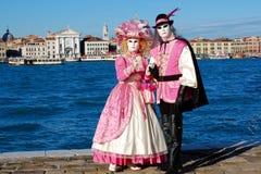 Όμορφο ζεύγος στα ζωηρόχρωμες κοστούμια και τις μάσκες, άποψη στην πλατεία SAN Marco Στοκ Εικόνες