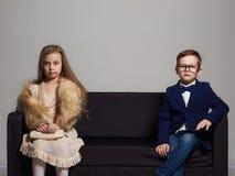 Όμορφο ζεύγος στον καναπέ μικρό κορίτσι και αγόρι ομορφιάς kids stylish Στοκ Φωτογραφία