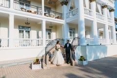 Όμορφο ζεύγος των newlyweds που περπατά σε ένα πάρκο με ένα όμορφο άσπρο κτήριο Νέος νεόνυμφος σε ένα μαύρο κοστούμι και νύφη Στοκ εικόνα με δικαίωμα ελεύθερης χρήσης