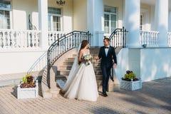 Όμορφο ζεύγος των newlyweds που περπατά σε ένα πάρκο με ένα όμορφο άσπρο κτήριο Νέος νεόνυμφος σε ένα μαύρο κοστούμι και νύφη Στοκ εικόνες με δικαίωμα ελεύθερης χρήσης