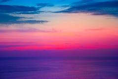 Όμορφο ζωηρόχρωμο κάψιμο ηλιοβασιλέματος ουρανού πέρα από τη θάλασσα στο λυκόφως Στοκ Εικόνες