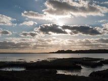 Όμορφο ηλιοβασίλεμα άνω του Λα σκιαγραφιών σύννεφων κόλπων θάλασσας λιμενικών ακτών Στοκ Φωτογραφία