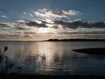 Όμορφο ηλιοβασίλεμα άνω του Λα σκιαγραφιών σύννεφων κόλπων θάλασσας λιμενικών ακτών Στοκ Εικόνες