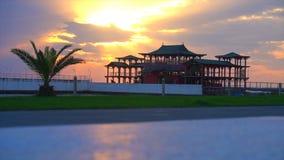 Όμορφο ηλιοβασίλεμα ενάντια στο σκηνικό των φοινίκων και του κινεζικού σπιτιού απόθεμα βίντεο