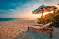 όμορφο ηλιοβασίλεμα παρ&a Έδρες στην αμμώδη παραλία κοντά στη θάλασσα Έννοια καλοκαιρινών διακοπών και διακοπών Εμπνευσμένη τροπι Στοκ εικόνα με δικαίωμα ελεύθερης χρήσης