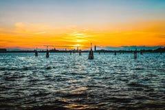Όμορφο ηλιοβασίλεμα στη θάλασσα με τις ξύλινες αποβάθρες στο νερό και τις απόψεις της Βενετίας, Lido, Ιταλία στοκ φωτογραφίες