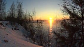 Όμορφο ηλιοβασίλεμα στον παγωμένο ποταμό το χειμώνα απόθεμα βίντεο