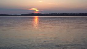 Όμορφο ηλιοβασίλεμα στο μεγάλο ποταμό, τα εγκαύματα πορειών ήλιων με το χρυσό, απόθεμα βίντεο