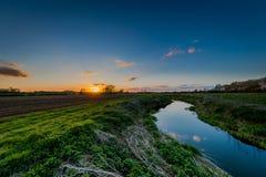 Όμορφο ηλιοβασίλεμα βραδιού πέρα από τους τομείς από έναν ποταμό Στοκ εικόνα με δικαίωμα ελεύθερης χρήσης