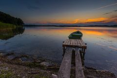 Όμορφο ηλιοβασίλεμα λιμνών με τη βάρκα ψαράδων Στοκ Εικόνα