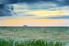 Όμορφο ηλιοβασίλεμα με ένα κρουαζιερόπλοιο που πλέει μακριά με τον ορίζοντα με την πράσινη χλόη στο πρώτο πλάνο Σύλληψη διακοπών Στοκ Εικόνες