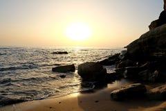 Όμορφο ηλιοβασίλεμα πέρα από τη θάλασσα και τους βράχους Στοκ Φωτογραφίες