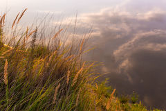 Όμορφο ηλιοβασίλεμα πέρα από τον ποταμό Παραλία με τη χλόη, τις εγκαταστάσεις και sedge στο φως του ήλιου αντανάκλαση των σύννεφω Στοκ Εικόνες