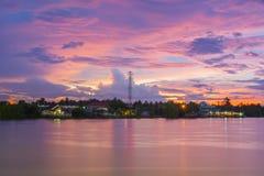 Όμορφο ηλιοβασίλεμα σε μια τροπική χώρα πέρα από τον ποταμό, με τον πύργο τηλεπικοινωνιών Στοκ εικόνες με δικαίωμα ελεύθερης χρήσης