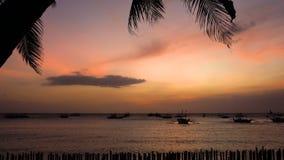 Όμορφο ηλιοβασίλεμα στην παραλία με τους φοίνικες και τις βάρκες απόθεμα βίντεο