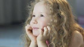 Όμορφο θηλυκό παιδί που βρίσκεται στο πάτωμα και που ονειρεύεται, πίστη σε ένα θαύμα απόθεμα βίντεο