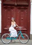 Όμορφο θηλυκό στην άσπρη τοποθέτηση φορεμάτων στο μπλε εκλεκτής ποιότητας ποδήλατο μπροστά από τις όμορφες παλαιές κόκκινες πόρτε στοκ εικόνες
