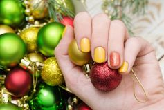 Όμορφο θηλυκό χέρι με το κίτρινο σχέδιο καρφιών Μανικιούρ Χριστουγέννων στοκ φωτογραφίες