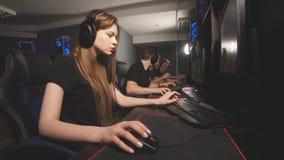Όμορφο θηλυκό gamer που φορά την κάσκα, που παίζει στο σε απευθείας σύνδεση τηλεοπτικό παιχνίδι απόθεμα βίντεο