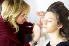 Όμορφο θηλυκό πρότυπο που παίρνει makeup πριν από το πυροβολισμό Στοκ εικόνες με δικαίωμα ελεύθερης χρήσης