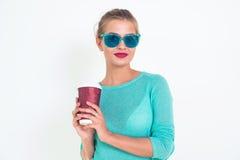 Όμορφο θηλυκό φλυτζάνι εκμετάλλευσης του καυτού καφέ για να πάει, που φορά τα μοντέρνα μπλε γυαλιά ηλίου, την μπλούζα και τη φωτε στοκ φωτογραφία με δικαίωμα ελεύθερης χρήσης