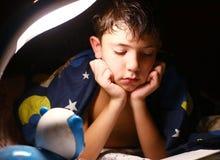 Όμορφο διαβασμένο αγόρι βιβλίο Preteen με το λαμπτήρα πριν από τον ύπνο Στοκ Φωτογραφίες