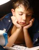 Όμορφο διαβασμένο αγόρι βιβλίο Preteen με το λαμπτήρα πριν από τον ύπνο Στοκ Φωτογραφία