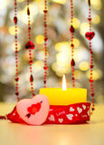 Όμορφο κίτρινο καίγοντας κερί ημέρας βαλεντίνων του ST δίπλα σε μια κόκκινη καρδιά και κόκκινες χάντρες Στοκ φωτογραφία με δικαίωμα ελεύθερης χρήσης