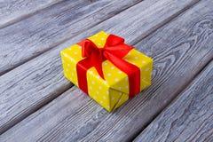 Όμορφο κίτρινο κιβώτιο δώρων με μια κόκκινη κορδέλλα Στοκ Φωτογραφία