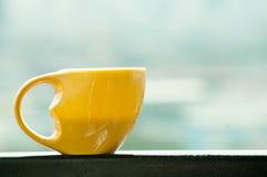 Όμορφο κίτρινο φλυτζάνι καφέ με το ανοικτό μπλε υπόβαθρο θαμπάδων Στοκ Φωτογραφία