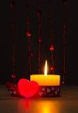 Όμορφο καίγοντας κερί ημέρας βαλεντίνων του ST δίπλα σε μια κόκκινη καρδιά και τις χάντρες Στοκ Εικόνα