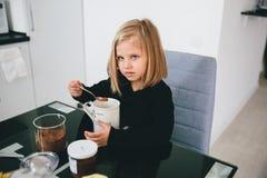 Όμορφο και γλυκό κακάο μαγείρων κοριτσιών στον πίνακα στοκ εικόνες