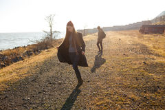 Όμορφο και μοντέρνο ζεύγος που περπατά σε μια δύσκολη παραλία Το ζεύγος έντυσε στα σακάκια, τα καπέλα και τις μπότες Στοκ φωτογραφίες με δικαίωμα ελεύθερης χρήσης