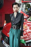 Όμορφο και μοντέρνο κορίτσι Α σε μια μαύρη μπλούζα, πράσινα εσώρουχα, εκλεκτής ποιότητας σκουλαρίκια chanel που θέτουν κατά τη δι Στοκ Εικόνες