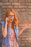 Όμορφο και ταραγμένο redhead καυκάσιο κορίτσι που μιλά στο έξυπνο τηλέφωνο στοκ εικόνα