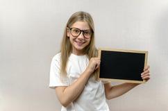 Όμορφο κακό κορίτσι με τα γυαλιά που κρατά ένα σημάδι στα χέρια της αντίγραφο-διάστημα στοκ εικόνα
