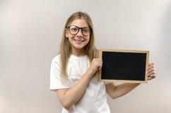 Όμορφο κακό κορίτσι με τα γυαλιά που κρατά ένα σημάδι στα χέρια της αντίγραφο-διάστημα στοκ φωτογραφία