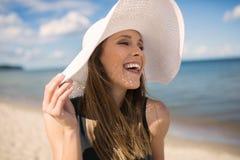 Όμορφο καπέλο εκμετάλλευσης γυναικών που φαίνεται μακριά γελώντας Στοκ Εικόνες