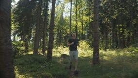 Όμορφο καυκάσιο άτομο που τρέχει σε ένα δάσος κατά τη διάρκεια της ηλιόλουστης ημέρας απόθεμα βίντεο