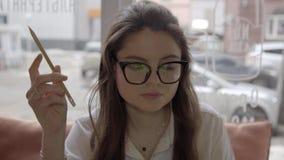 Όμορφο καυκάσιο κορίτσι στα γυαλιά που λειτουργούν σε έναν καφέ και έναν καφέ κατανάλωσης, που παίζουν με το pensil απόθεμα βίντεο
