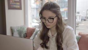 Όμορφο καυκάσιο κορίτσι στα γυαλιά που λειτουργούν σε έναν καφέ με το lap-top απόθεμα βίντεο