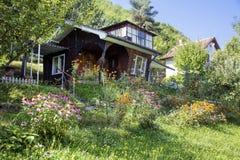 Όμορφο καφετί ξύλινο σπίτι με το μεγάλο πράσινο κήπο Στοκ Εικόνες