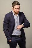 Όμορφο καλά-ντυμένο άτομο με τη γενειάδα που εξετάζει το wristwatch του Στοκ φωτογραφίες με δικαίωμα ελεύθερης χρήσης